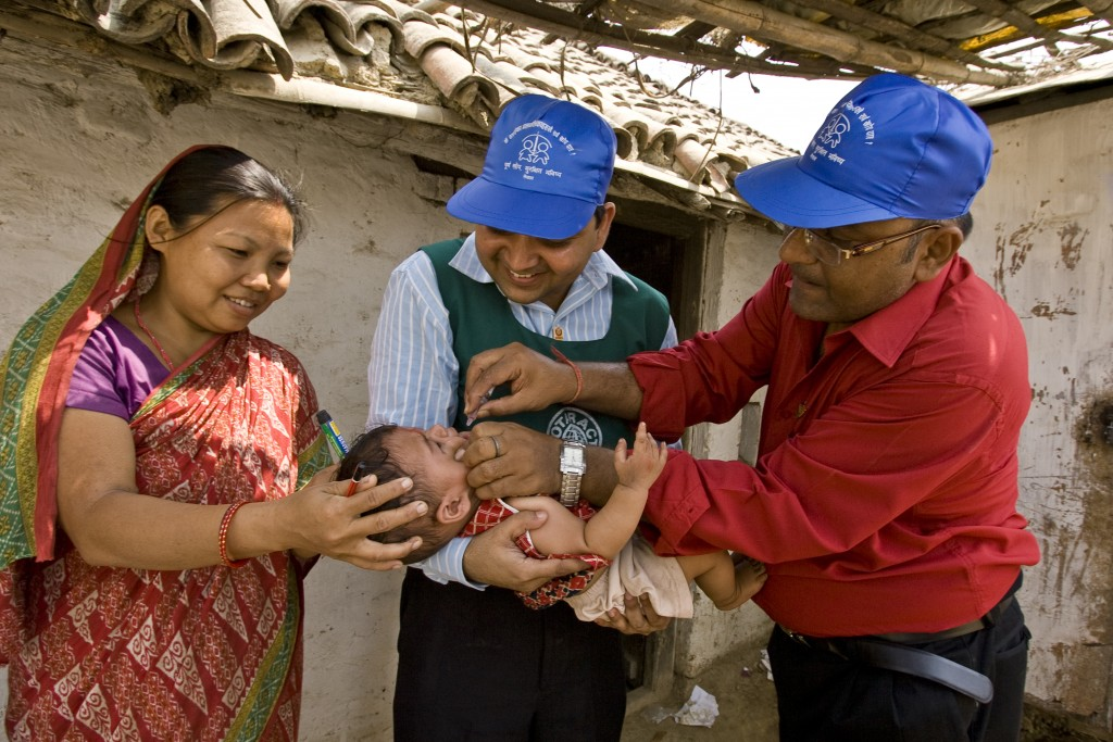 Abishek Choudhary, of the Rotaract Club of Birgunj, Nepal, holds a baby, while Rotarian Om Prakash Sikaria administers polio vaccine during a subnational polio immunization day. Border towns with little regulation like Birgunj create high risk of the spread of the poliovirus. Subnational immunization days take place more often than larger annual events and target strategic locations based on research by Rotary's polio eradication partners, the World Health Organization, UNICEF, and the U.S. Centers for Disease Control.